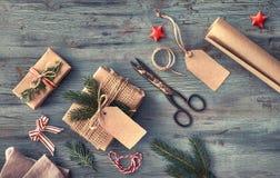 Passi i regali elaborati sulla tavola di legno rustica scura con il Natale de Immagine Stock