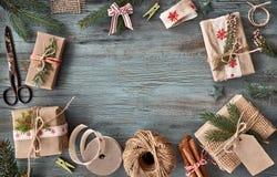 Passi i regali elaborati sulla tavola di legno rustica scura con il Natale de Fotografia Stock