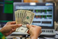 Passi i soldi della tenuta con esposizione del monitor del mercato azionario sui precedenti Fotografia Stock Libera da Diritti