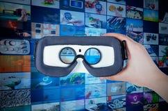 Passi i vetri di realtà virtuale della tenuta con il flusso continuo nel backgroun immagini stock libere da diritti