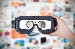 Passi i vetri di realtà virtuale della tenuta con il flusso continuo nel fondo immagine stock libera da diritti