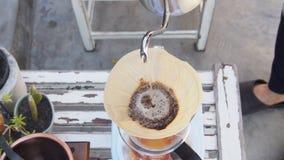 Passi il caffè americano, barista che versa l'acqua calda sopra la polvere grinded arrostita del caffè che fa il gocciolamento pe Fotografia Stock Libera da Diritti