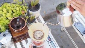 Passi il caffè americano, barista che versa l'acqua calda sopra la polvere grinded arrostita del caffè che fa il gocciolamento pe Immagini Stock Libere da Diritti