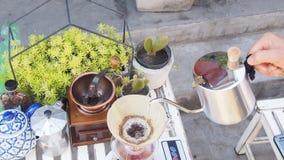 Passi il caffè americano, barista che versa l'acqua calda sopra la polvere grinded arrostita del caffè che fa il gocciolamento pe Fotografie Stock Libere da Diritti