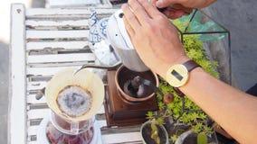 Passi il caffè americano, barista che versa l'acqua calda sopra la polvere grinded arrostita del caffè che fa il gocciolamento pe Fotografie Stock