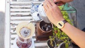 Passi il caffè americano, barista che versa l'acqua calda sopra la polvere grinded arrostita del caffè che fa il gocciolamento pe Immagine Stock