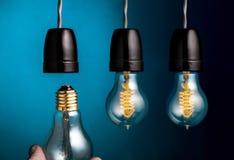 Passi il cambiamento del filamento antico di stile di edison lampadine su dar immagine stock