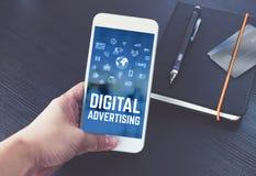 Passi il cellulare della tenuta che parla con la pubblicità digitale sullo schermo w fotografie stock libere da diritti