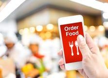 Passi il cellulare della tenuta con l'alimento di ordine online con il ristorante della sfuocatura Fotografia Stock