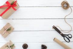 Passi il contenitore e gli strumenti di regali elaborati del regalo di Natale su fondo di legno bianco Fotografie Stock Libere da Diritti