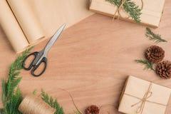 Passi il contenitore e gli strumenti di regali elaborati del regalo di Natale sul BAC di legno Immagini Stock