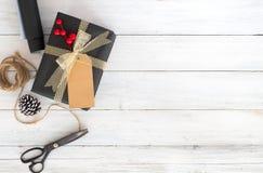 Passi il contenitore e gli strumenti di regalo elaborati del regalo di Natale su fondo di legno bianco Fotografie Stock