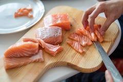 Passi il cuoco unico che usando la fetta del coltello salmone crudo sul tagliere Immagine Stock Libera da Diritti