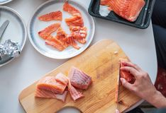 Passi il cuoco unico che usando la fetta del coltello salmone crudo sul tagliere Immagini Stock Libere da Diritti
