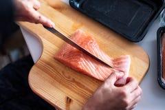 Passi il cuoco unico che usando la fetta del coltello salmone crudo sul tagliere Fotografia Stock