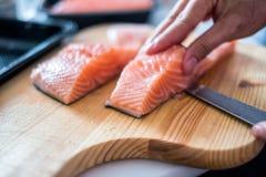 Passi il cuoco unico che usando la fetta del coltello salmone crudo sul tagliere Immagine Stock
