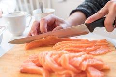 Passi il cuoco unico che usando la fetta del coltello salmone crudo sul tagliere Immagini Stock