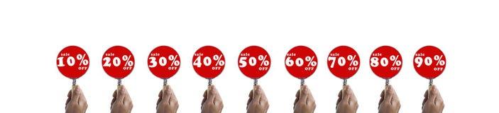 Passi il fuoco della lente d'ingrandimento della tenuta sull'insieme di simboli di vendita a ribasso Fotografia Stock