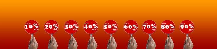 Passi il fuoco della lente d'ingrandimento della tenuta sull'insieme di simboli di vendita a ribasso Immagini Stock