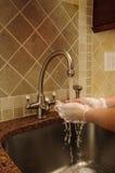 Passi il lavaggio e la sciacquatura dell'acqua insaponata ad un dispersore Fotografie Stock