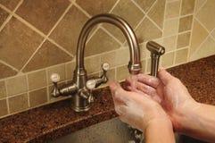 Passi il lavaggio sotto l'acqua che scorre fuori un rubinetto Fotografia Stock