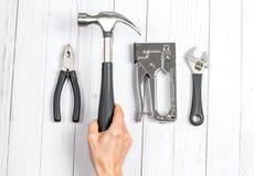 Passi il martello della holding Strumenti, chiavi e pinze su un fondo bianco immagine stock libera da diritti