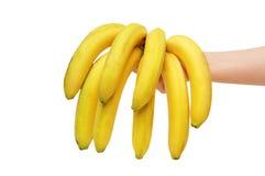 Passi il mazzo della holding di banane isolate su bianco Fotografie Stock