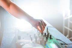 Passi il miscelatore di musica del DJ in night-club sul partito con incandescenza luminosa Immagini Stock