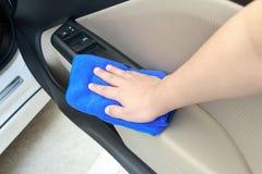Passi il pannello interno di pulizia della porta di automobile con il panno del microfiber Fotografia Stock Libera da Diritti