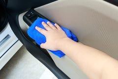 Passi il pannello interno di pulizia della porta di automobile con il panno del microfiber Immagini Stock