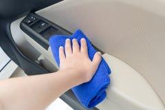 Passi il pannello interno di pulizia della porta di automobile con il panno del microfiber Fotografie Stock