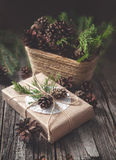 Passi il regalo elaborato su fondo di legno rustico e un canestro con i rami ed i coni dell'abete Fotografie Stock