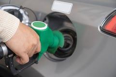 Passi il riempimento dell'automobile con combustibile alla stazione di rifornimento di carburante Automobile grigia alla stazione fotografia stock
