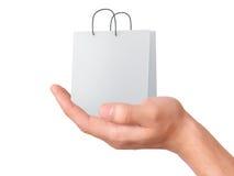 Passi il sacchetto di acquisto della holding Concetto di vendita - mano con la lente d'ingrandimento Fotografie Stock