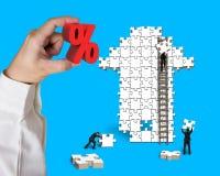 Passi il segno di percentuale della tenuta con gli uomini d'affari che costruiscono il puzzle della freccia Fotografia Stock