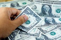 Passi il selezionamento della banconota del dollaro americano dalla pila di banconote sulla f Fotografia Stock Libera da Diritti