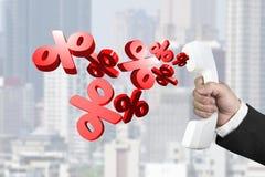 Passi il telefono della tenuta con i segni di percentuale che spruzzano il ou Fotografia Stock