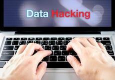 Passi il tipo sul computer portatile con i dati che incidono sullo schermo con il backgr della sfuocatura Fotografie Stock Libere da Diritti