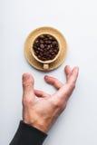 Passi l'allungamento ad una tazza di caffè su un fondo bianco, versato Fotografie Stock