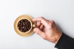 Passi l'allungamento ad una tazza di caffè su un fondo bianco, versato Immagini Stock