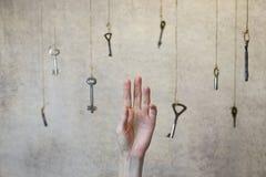 Passi l'allungamento per una delle molte chiavi d'annata vecchie Immagine Stock