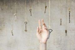 Passi l'allungamento per una delle molte chiavi d'annata vecchie Fotografia Stock