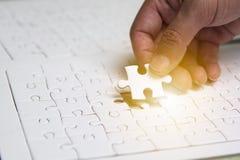 Passi l'inserimento del puzzle mancante per fare l'immagine completa fotografie stock libere da diritti