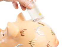 Passi l'inserimento della banconota in un porcellino salvadanaio, concetto dell'euro cinquanta per l'affare e risparmi i soldi Fotografia Stock