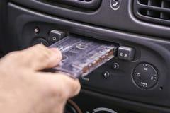 Passi l'inserimento della cassetta di musica nel riproduttore audio anziano dell'automobile Fotografia Stock Libera da Diritti