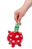 Passi l'inserimento della moneta nel porcellino salvadanaio Fotografia Stock Libera da Diritti
