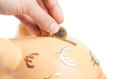 Passi l'inserimento della moneta in un porcellino salvadanaio, concetto per l'affare e risparmi i soldi Fotografia Stock Libera da Diritti
