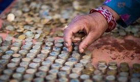 Passi l'organizzazione delle monete nella colonna di impilamento, Nepal Fotografia Stock Libera da Diritti