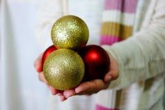 Passi l'oro della tenuta e l'ornamento rosso con il maglione e la sciarpa bianchi Fotografia Stock