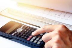 Passi l'uomo che fa le finanze con usando l'ufficio del calcolatore a casa Immagini Stock